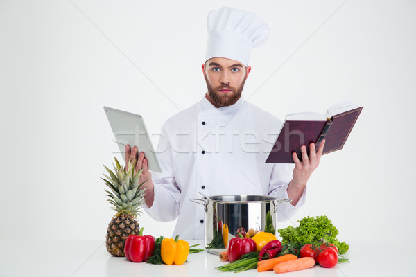 ?ale chef cook holding table computer and recipe book  Stock photo © deandrobot