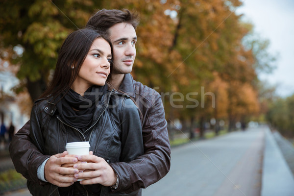 Couple with coffee looking away outdoors Stock photo © deandrobot