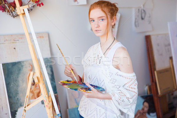 Thoughtful female painter using oil paints for painting on canvas Stock photo © deandrobot
