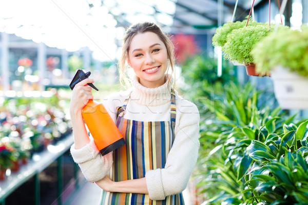 Cheerful attractive woman gardener standing in orangery with water pulverizer Stock photo © deandrobot