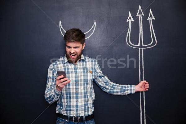 красивый мужчина играет роль дьявол Постоянный доске Сток-фото © deandrobot