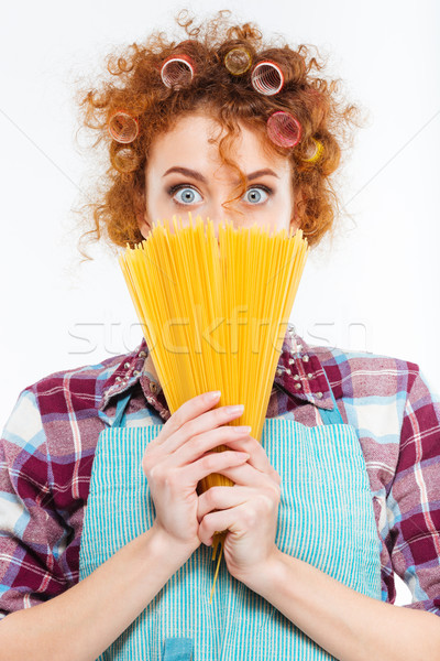 Wondered housewife covered face with uncooked spagetti  Stock photo © deandrobot