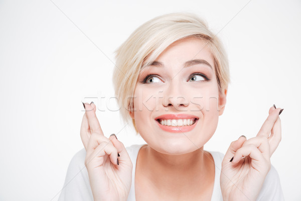 Stock photo: Smiling woman with fingers crossed gesture