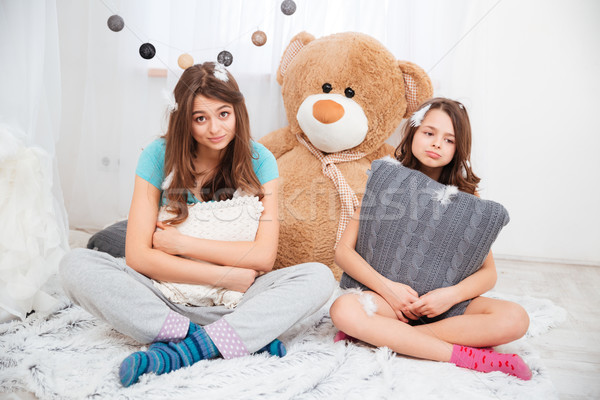 Two sad tired sisters sitting and hugging pillows Stock photo © deandrobot