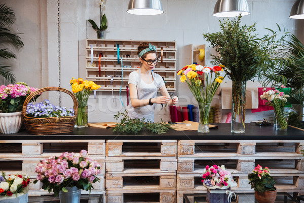 Cute concentrated female florist working in flower shop Stock photo © deandrobot