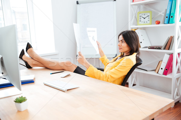 Businesswoman reading report papers in office Stock photo © deandrobot