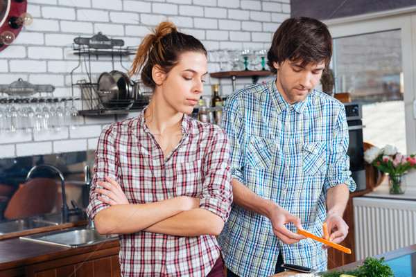 Strict unhappy woman cooking with her husband on kitchen  Stock photo © deandrobot