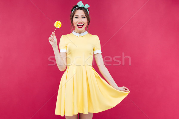 Cheerful cute pinup girl standing and holding yellow lollipop Stock photo © deandrobot