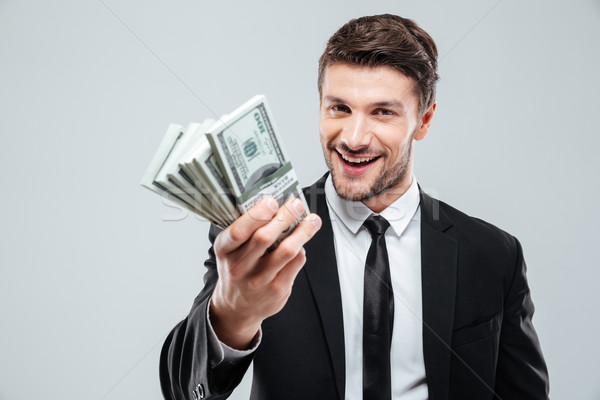 Closeup of cheerful young businessman holding money Stock photo © deandrobot