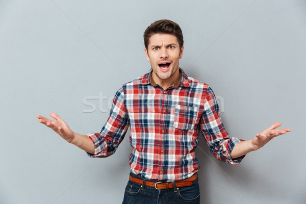 Angry irritated young man in t-shirt Stock photo © deandrobot