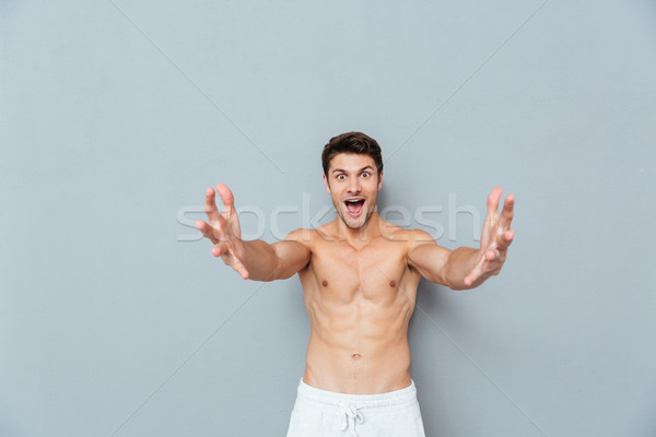 Happy excited young man with opened hands ready for hugging Stock photo © deandrobot