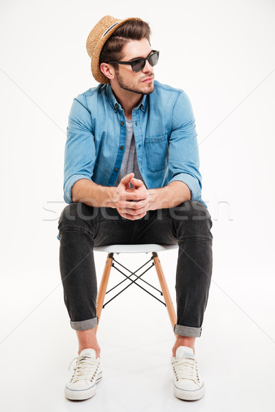 Töprengő fiatalember ül szék gondolkodik kalap Stock fotó © deandrobot