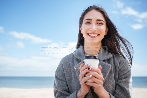 Close-up portrait of a smiling girl holding takeaway cup Stock photo © deandrobot