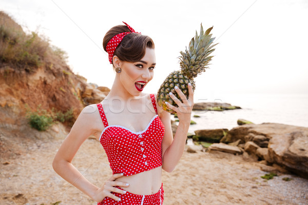 Beautiful pin up diva holding pineapple with mouth open Stock photo © deandrobot