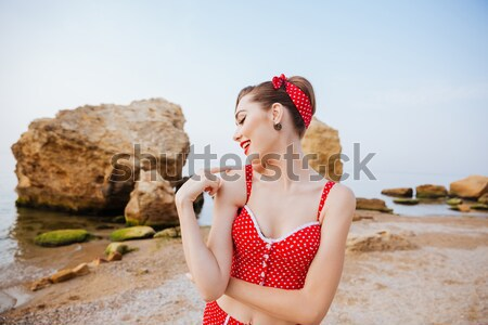 Smiling beautiful pinup girl in headband posing with pineapple Stock photo © deandrobot