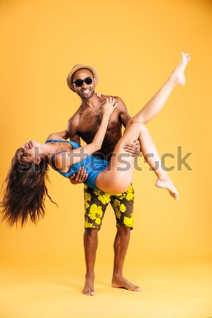 African man in swimwear shooting with water gun Stock photo © deandrobot