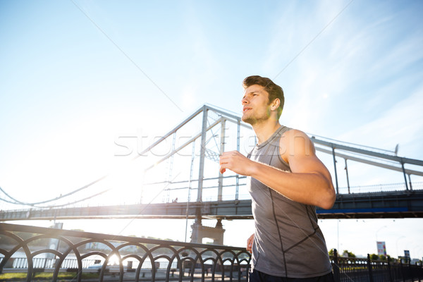 Handsome sports man running along modern bridge at sunset light Stock photo © deandrobot