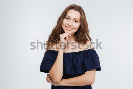 Portrait of cheerful attractive young woman standing with hands folded Stock photo © deandrobot