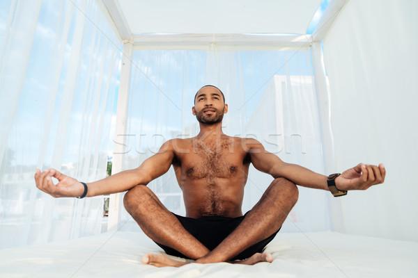 Jóképű fiatal afrikai férfi rövidnadrág ül Stock fotó © deandrobot