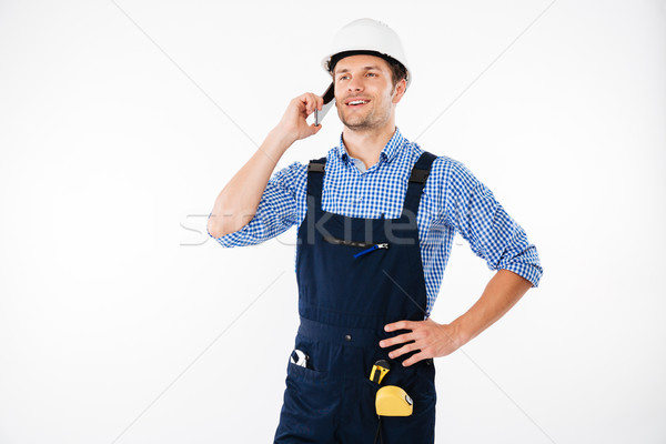 Handsome young builder in overall talking on mobile phone Stock photo © deandrobot
