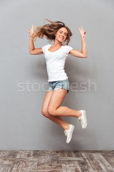 Portrait of a cheerful woman jumping and showing v gesture Stock photo © deandrobot