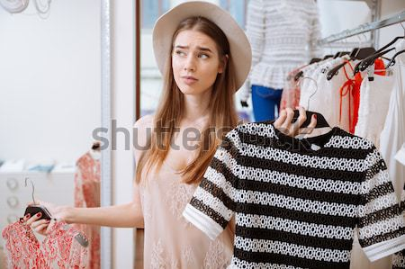 Attractive young woman trying on dress in front of mirror Stock photo © deandrobot