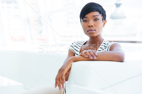 Concentrated african young woman accountant sitting in office Stock photo © deandrobot