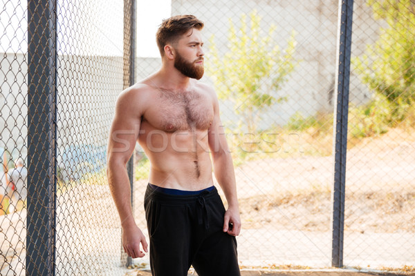 Handsome shirtless fitness man during workout outdoors Stock photo © deandrobot
