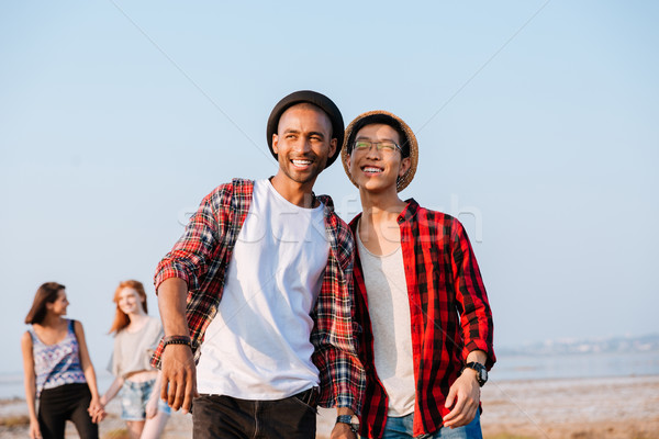 Two happy young men standing and looking far away outdoors Stock photo © deandrobot