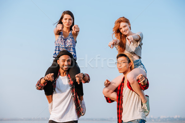Smiling women sitting at boyfriends shoulders and pointing on you Stock photo © deandrobot