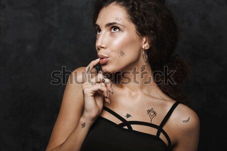 Beautiful african young woman with stylish makeup sitting on chair Stock photo © deandrobot