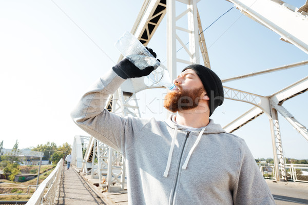 Portrait of a young bearded athlete in sportswear drinking water Stock photo © deandrobot