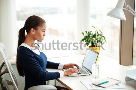 Smiling african business woman with documents looking away Stock photo © deandrobot