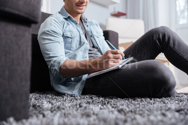 Man writting in copybook while sitting on the carpet Stock photo © deandrobot