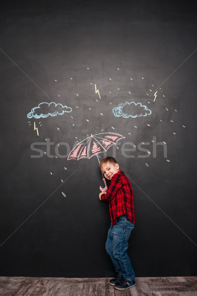 Cheerful kid holding umbrella on chalkboard with drawings of rain Stock photo © deandrobot