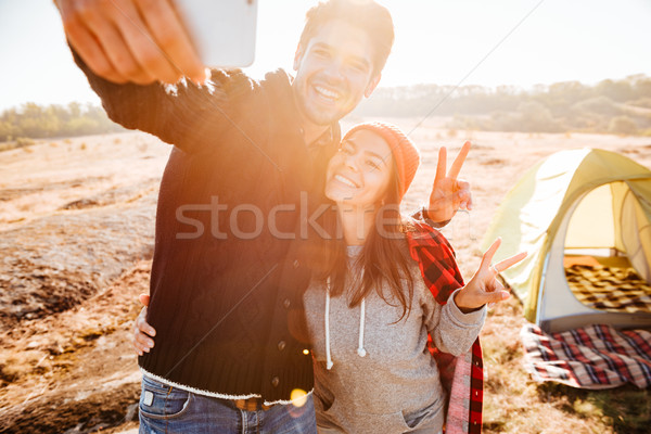 Young couple making selfie while standing at campsite Stock photo © deandrobot
