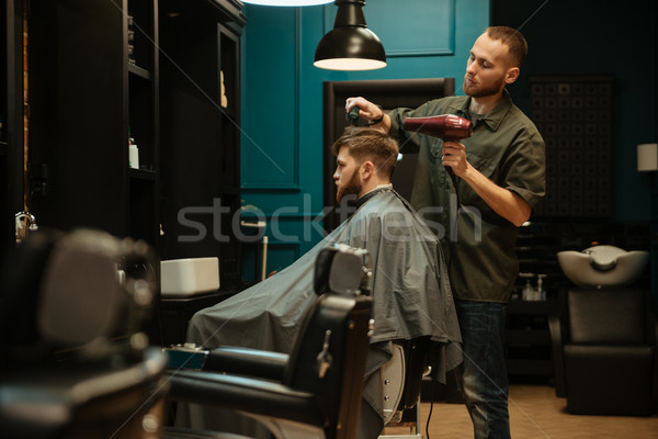 Side view of hairdresser using hair dryer and hairbrush Stock photo © deandrobot