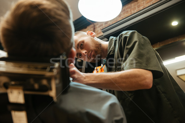 Young man getting beard haircut by hairdresser Stock photo © deandrobot