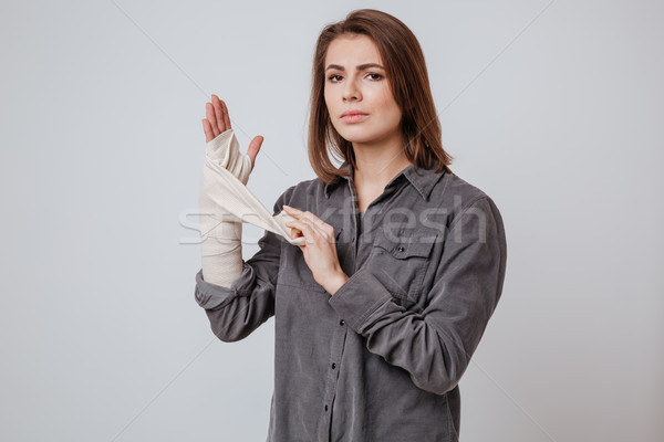 Sick young lady with the plaster on hand Stock photo © deandrobot