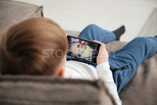 Back view photo of little boy holding smartphone Stock photo © deandrobot