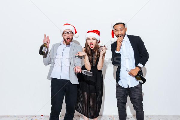 Três engraçado maravilhado pessoas garrafa Foto stock © deandrobot