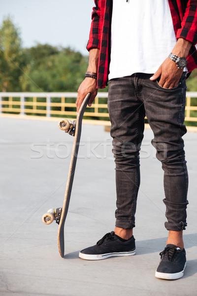 Young dark skinned man holding the skateboard Stock photo © deandrobot