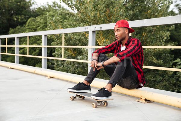 Jóvenes oscuro hombre sesión skateboard Foto Foto stock © deandrobot