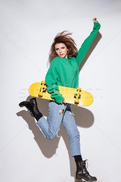 Skater woman jumping over white background. Stock photo © deandrobot