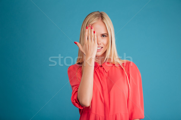Happy blonde young woman covering her eye with palm Stock photo © deandrobot
