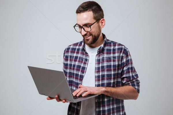Smiling Bearded man in eyeglases using laptop Stock photo © deandrobot