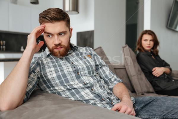 Sad quarrel loving couple sitting on sofa indoors Stock photo © deandrobot