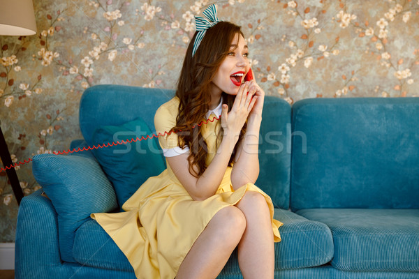 Cheerful young pin-up lady talking by phone. Stock photo © deandrobot