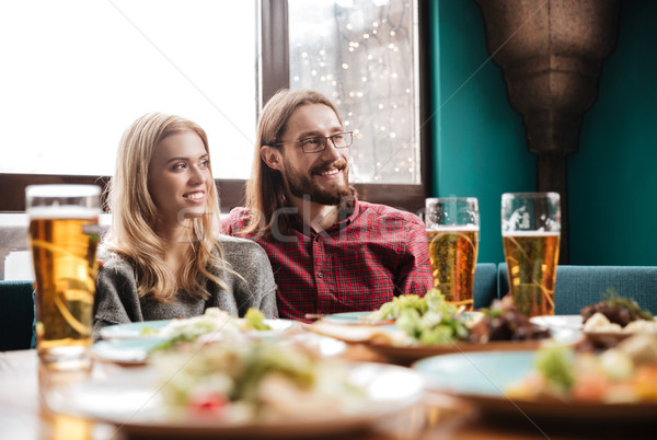 Stock photo: Happy friends sitting in cafe while eating and drinking alcohol