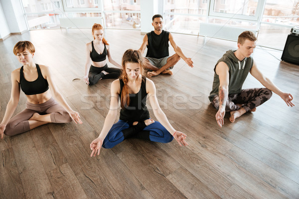 Group of people relaxing and meditating in lotus pose Stock photo © deandrobot